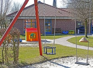 School playground. Swings with school in the background.